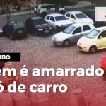 Vídeo mostra refém de assalto a banco amarrado em capô de carro
